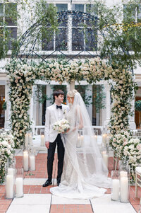 Bride and groom under ceremony floral arch