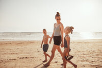 smiling-mom-and-her-kids-walking-along-a-sandy-bea-U5U8JEL-2048x1365