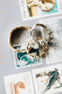 Engagement ring and wedding bands laying across vintage stamps