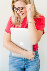 woman smiling and holding laptop