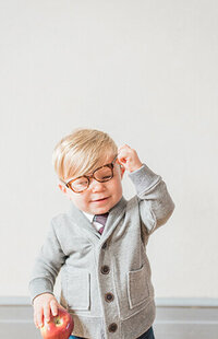 Toddler boy takes off his glasses