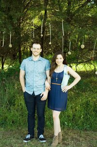 Sandra and Dylan linking arms and looking at the camera in front of some tall grass