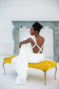 A bride sits on yellow bench in front of a mantel.