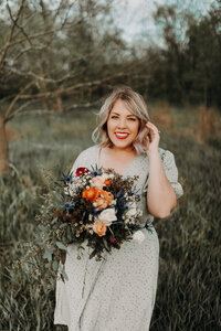 woman smiling and holding bridal bouquet