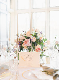 Luxury floral arrangement on the wedding breakfast table of blush and ivory roses and hydrangea