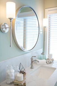 master bathroom remodel with round silver mirror