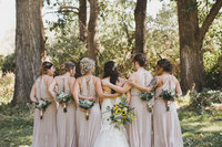 Bridesmaids and bride standing with the back of dresses and flowers showing