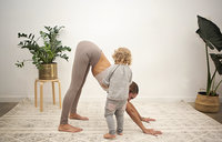 Toddler girl helps mom make a downward dog in yoga class at Hotsource Yoga in Aptos