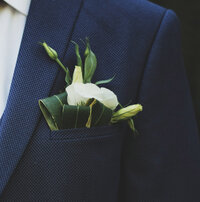 Groom in a blue suit with pinned flower
