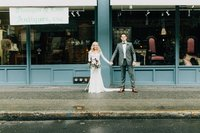 Bride and Groom hold hands in front of furniture store in downtown Seattle