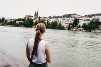 Woman with a long, blonde ponytail looking out over a river in Basel, Switzerland
