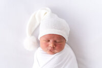 a sleeping baby is swaddled in white