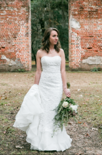 Portrait of a bride in her wedding dress with a bouquet of flowers held to her side standing in front at the center of two brick walls in savannah Georgia