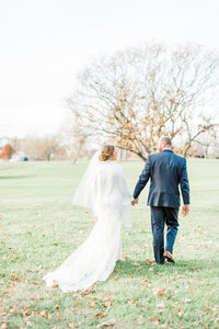 Bride and Groom Walking Through Field