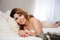 woman laying on a bed posing for a boudoir portrait at Boudoir & Pinup by Janet Lynn