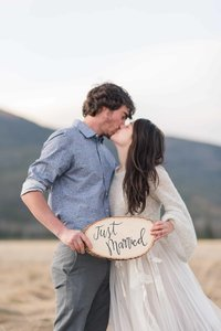 "Texas elopement photographer captures Georgia couple eloping in Colorado at Rocky Mountain National Park holding ""just married"" sign as they share a kiss"