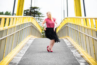 Hayley Maxwell a Copywriter in NZ dancing on a yellow bridge.