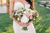 Bride holding bouquet by Chelan Floral during sunset wedding at The Lookout