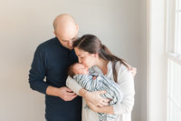 Mom kisses baby, Dad hugs mom by window during newborn photos