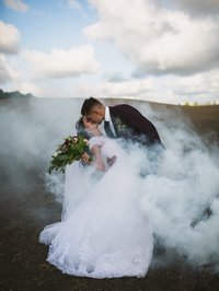Bride and Groom kissing with smoke