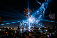 Fireworks and laser show in the sky over a crowd and lake at EPCOT Disney