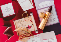 Flatlay image of wedding day details on top of red background