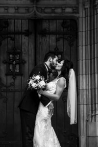 Bride and groom kissing outside the doors of the First Presbyterian Church of the Covenant in Erie, PA