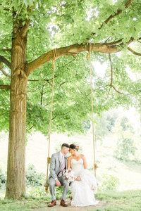 Bride and groom sitting on a tree swing at their summer Rivercrest Farm wedding photographed by akron ohio wedding photographer