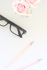 Flatlay of white desk with pens and glasses