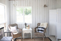 two wicker chairs with black bench in a white cottage