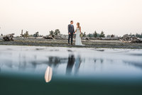 Wedding couple with their reflections on the ocean