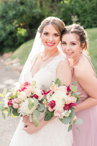 A bride poses with her maid of honor  at her California Mansion Wedding.