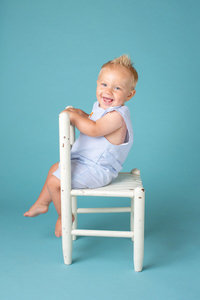 one year old baby boy smiling in a chair against a fun blue background