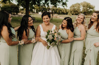 Bride and bridesmaids hugging and laughing