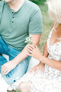 Engaged couple holding  small flowers .