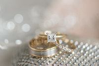 Stunning engagement ring resting on  a silver and gold wedding band.