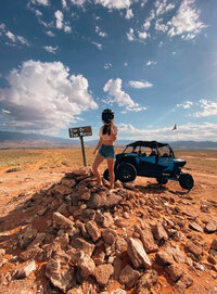 woman standing on a hill with a dune buggy