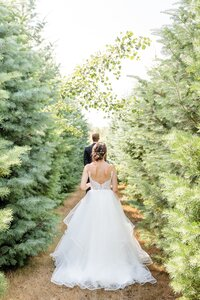 Bride-walks-up-in-anticipation-to-her-groom-with-his-back-turned-during-their-first-look-at-their-intimate-arrowwood-farms-wedding