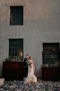 Groom stands behind bride has she hold bouquet in a dramatic photo on industrial wall