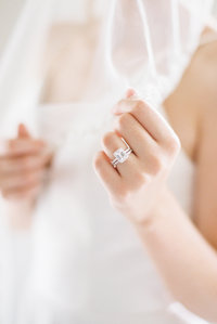 Emerald cut engagement ring on woman in wedding dress