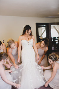 Bridesmaids smoothing out wedding gown