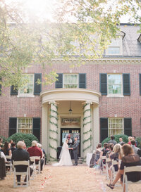 Bride and groom take their vows outdoors as guests look on