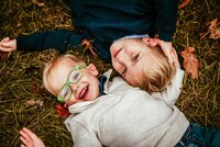 kids laughing in grass at a family photography session