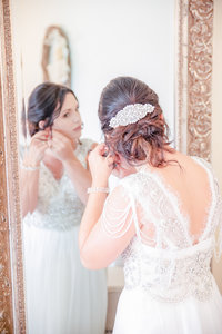 Bride adjusts her earrings in the mirror on her wedding day