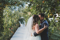 Bride and Groom hugging under greenery arch at Bella Fiori Gardens