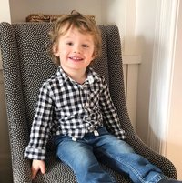 happy toddler in black and white shirt on chair