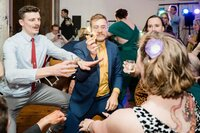 wedding guest dancing while eating donut