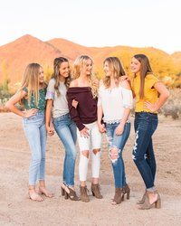 Group of senior girls standing and laughing in front of mountain in the desert