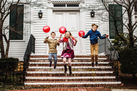 Kids jumping of church steps with red balloons
