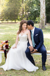 A bride and groom sit together in a park in East Austin
